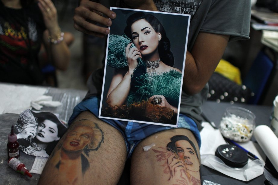Un homme tient une photo de la star burlesque Dita Von Teese alors qu'on s'apprête à lui tatouer cette photo sur la jambe lors de l'International Tattoo And Body Piercing Convention à Rio de Janeiro. | 7 janvier 2013