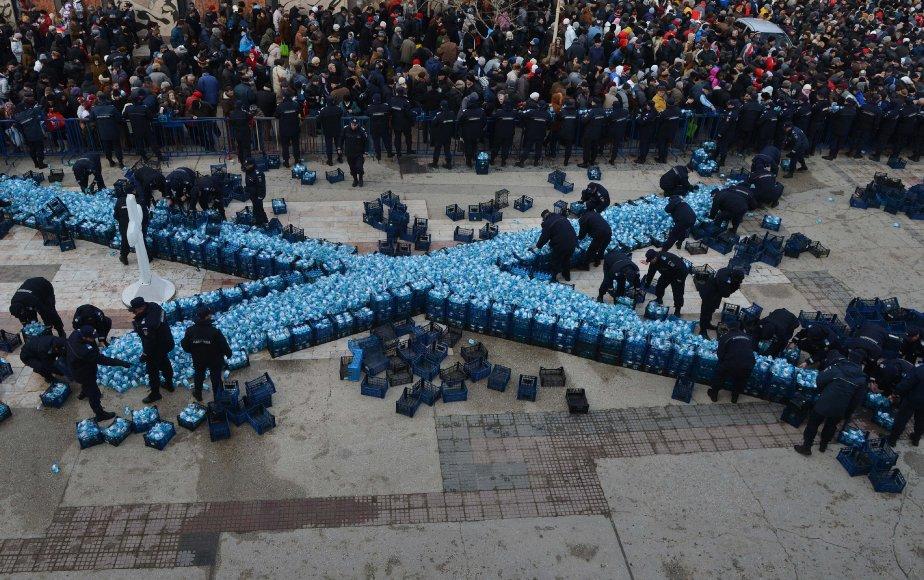 Des gendarmes roumains distribuent des bouteilles d'eau bénite après le service religieux de l'Épiphanie dans la ville de Constanta (230 km à l'est de Bucarest). | 7 janvier 2013
