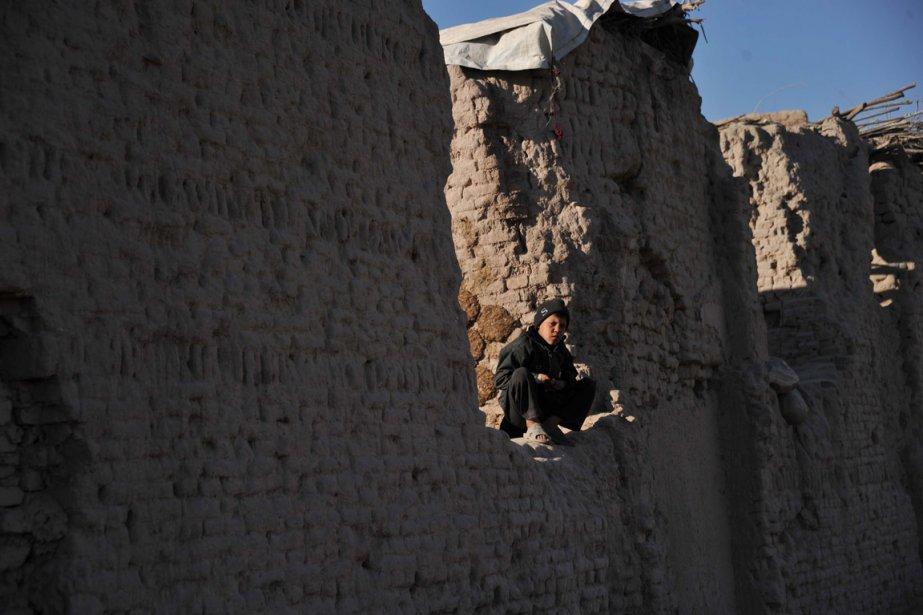 Un jeune garçon observe une partie de ghursai, jeu traditionnel afghan qui consiste à  renverser son adversaire tout en se tenant le pied d'une main. | 7 janvier 2013