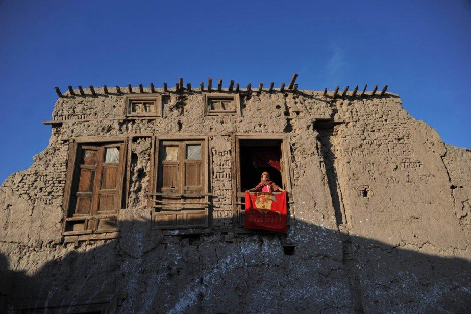 Une jeune Afghane observe les passants de la fenêtre de sa résidence en périphérie de Jalalabad, ville située à 150 kilomètres à l'est de Kaboul. | 7 janvier 2013