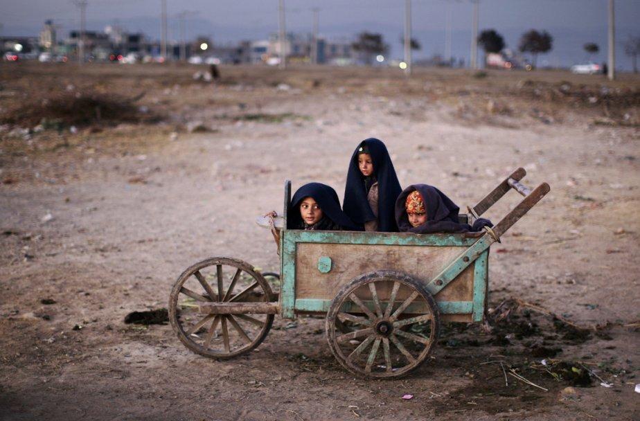 De jeunes réfugiés se protègent du froid dans un chariot de bois, à Jalalabad. | 7 janvier 2013