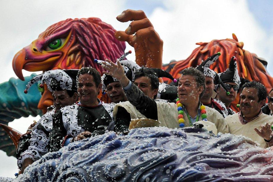 Le président colombien Juan Manuel Santos (deuxième à droite) salue la foule dans le défilé du jour des Blancs, au Carnaval des Noirs et des Blancs de Pasto, en Colombie. | 7 janvier 2013