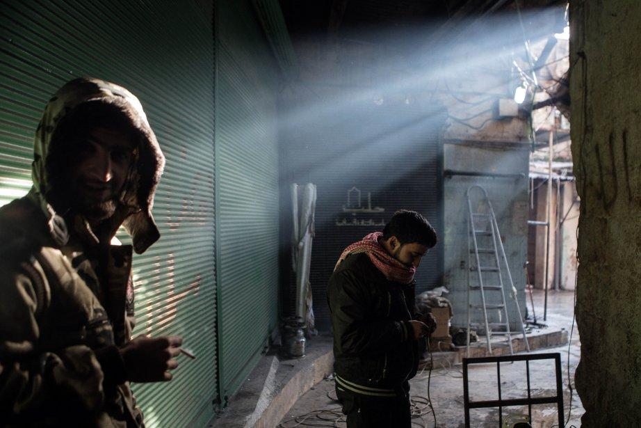 Un combattant rebelle (droite) s'apprête à monter un appareil photo sur une voiture afin d'espionner les forces gouvernementales syriennes, tandis que son camarade fume une cigarette dans le quartier Bab al-Nasr de la vieille ville d'Alep. | 8 janvier 2013