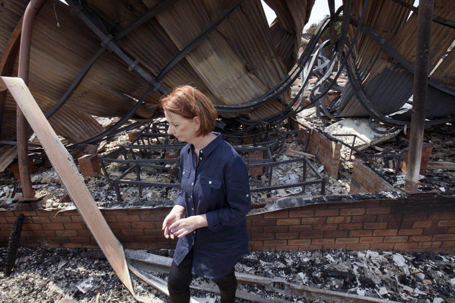 La première ministre australienne Julia Gillard observe les dégâts causés par les flammes dans une école de Dunnaly, en Tasmanie. | 8 janvier 2013