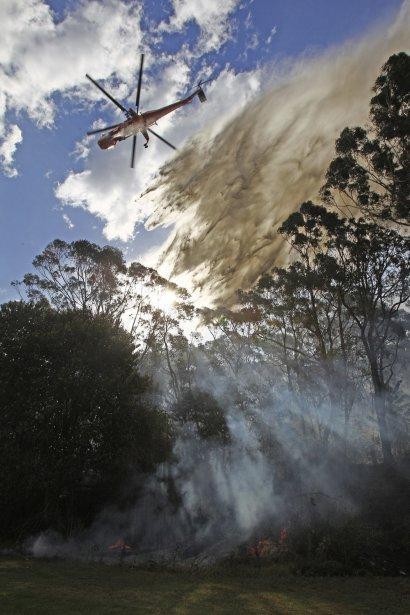 Un hélicoptère jette de l'eau sur un feu de brousse au parc national de Lane Cove, près de Sydney. | 8 janvier 2013