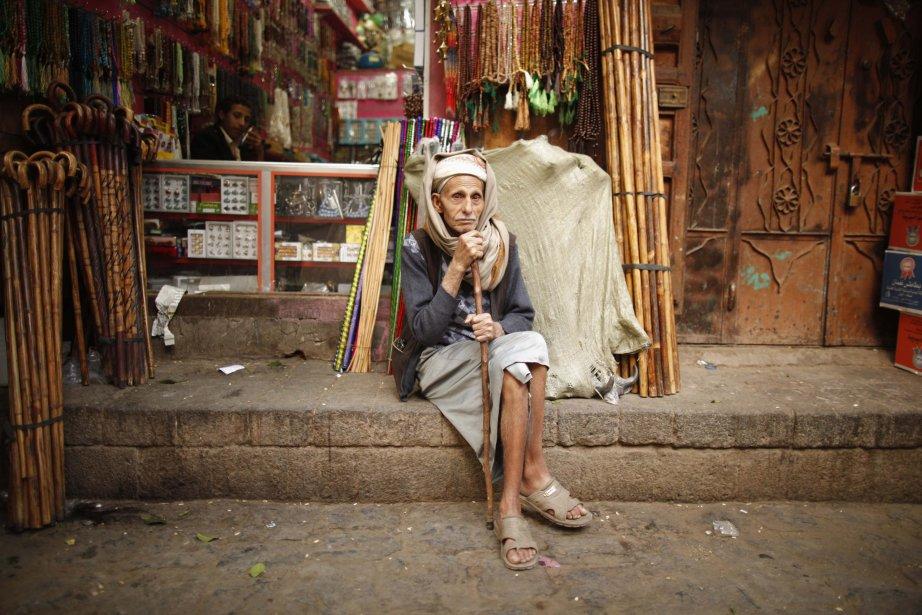 Un homme assis devant une échoppe au marché de la... | 2013-01-09 00:00:00.000