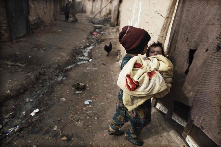 Une fillette tient son frère dans ses bras, dans un bidonville de la banlieue d'Islamabad, au Pakistan. | 9 janvier 2013