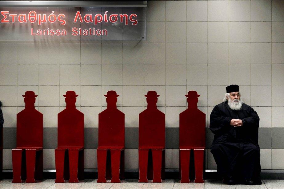 Un prêtre de l'Église grecque orthodoxe attend le métro à la station Larissa à Athènes. | 11 janvier 2013