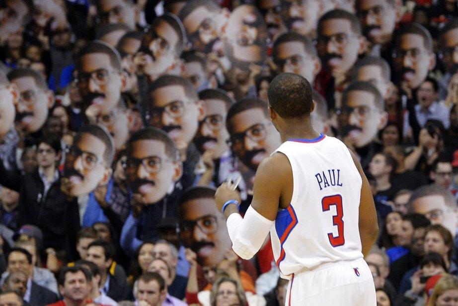 Chris Paul des Clippers de Los Angeles observe des partisans qui tiennent sa photo lors d'un match contre les Mavericks de Dallas à Los Angeles. | 11 janvier 2013