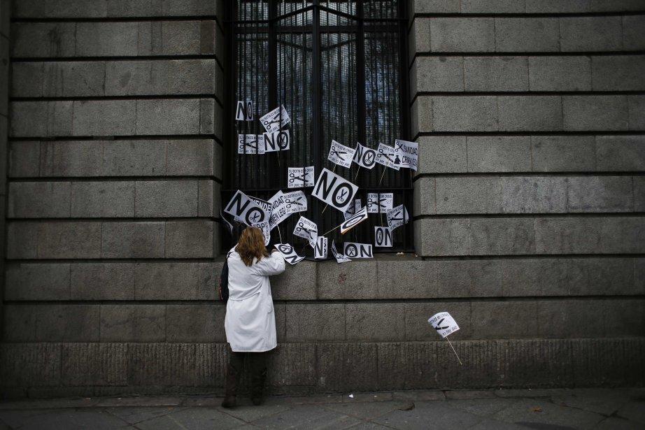 Une travailleuse de la santé pose une affiche dans une fenêtre du ministère de la Santé de l'Espagne après une manifestation contre coupes dans les dépenses de santé publique à Madrid. | 14 janvier 2013