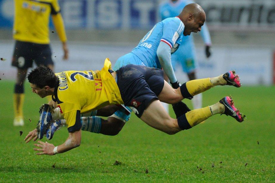 Le défenseur Sébastien Corchia (en jaune), du Sochaux de Montbéliard, et Ayew André, de l'Olympique de Marseille, entrent en collision lord du match de dimanche soir au stade August-Bonal, à Montbéliard. | 14 janvier 2013