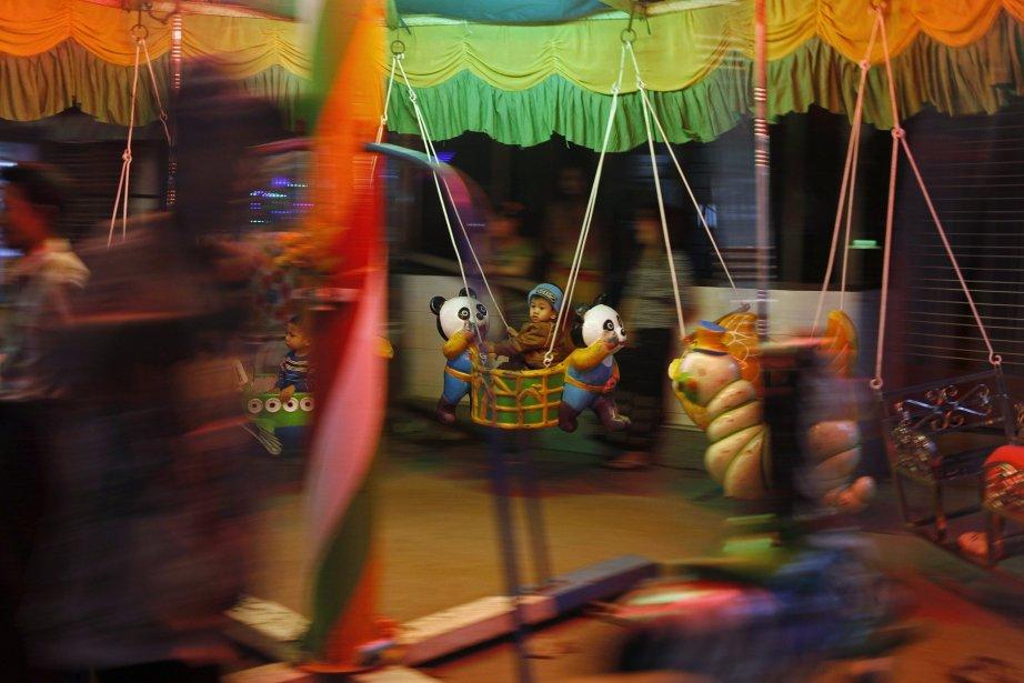 Un enfant dans un carrousel lors d'un festival de la pagode à Rangoun, en Birmanie. | 14 janvier 2013
