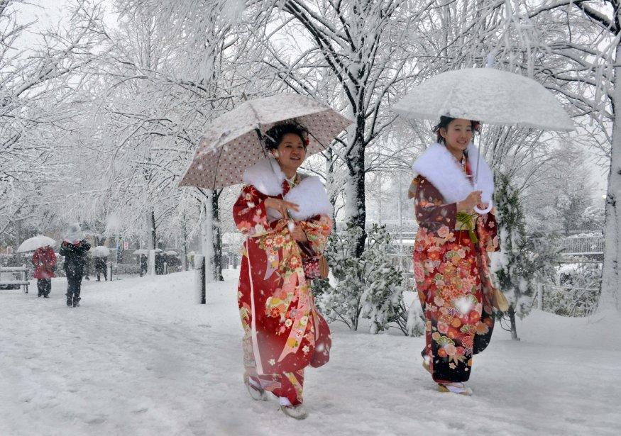 Deux jeunes femmes en kimono en route pour la cérémonie qui marque leur accession à la majorité (20 ans au Japon). Quelque 10 cm de neige ont complètement paralysé Tokyo lundi, du jamais vu depuis 2001, selon la chaîne de télévision japonaise NHK. | 15 janvier 2013