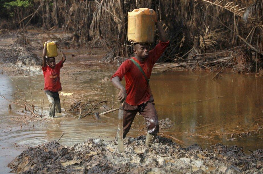Un homme et son fils transportent du pétrole dans les eaux polluées de la communauté de Kalaba. | 15 janvier 2013