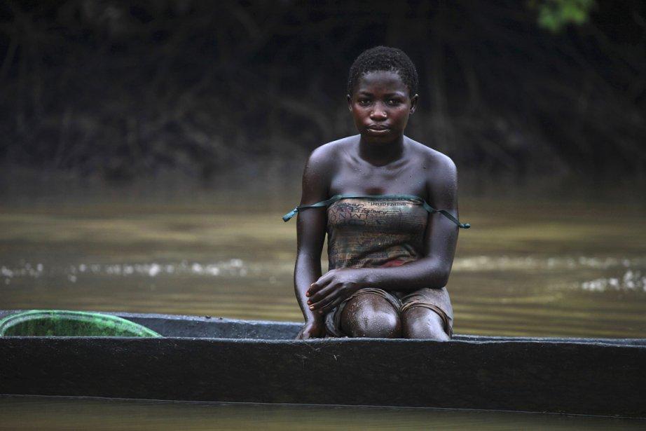 Une jeune femme du nom de Akpomene à bord de son canot sur lequel elle pêche non loin d'une raffinerie illégale. | 15 janvier 2013