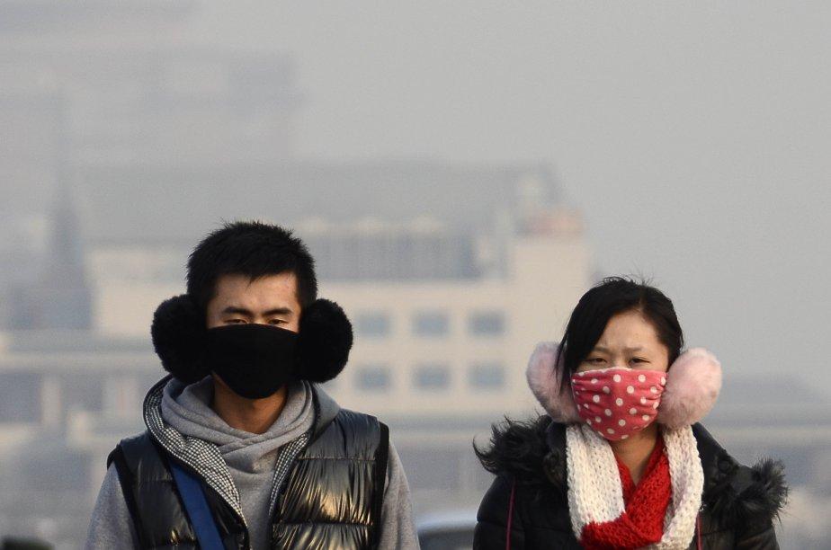 Un couple muni de masques antipollution dans une rue de Pékin. Les actions d'un fabricant de masques ont grimpé le 15 janvier, les investisseurs voulant tirer profit de la forte pollution atmosphérique qui sévit sur plusieurs parties de la Chine. | 16 janvier 2013