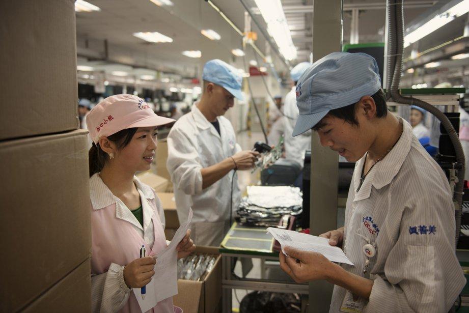Zhang Xuemei, 19 ans, une conseillère en relation de travail discute avec un employé de l'usine Quanta à Chongquing. | 17 janvier 2013