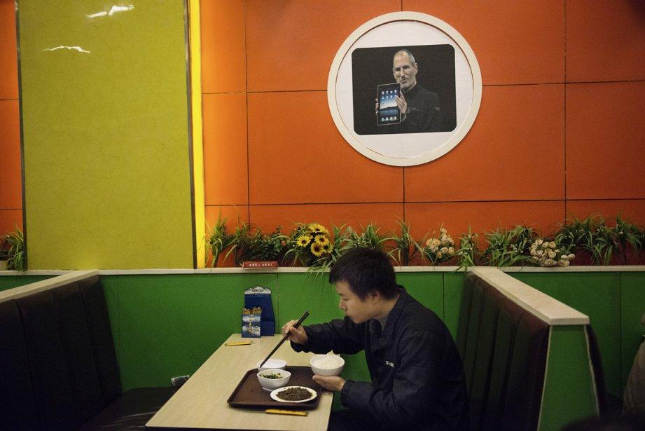 Foxconn est le plus important employeur privé de chine, ici, une employée  profite de sa pause de diner sous une affiche de Steve Jobs. | 17 janvier 2013