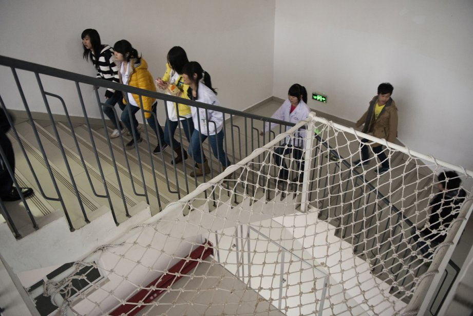 Des employées d'usine de fabrication de produits électronique passent un filet antisuicide installé dans la cage d'escalier d'un des dortoirs pour employés. | 17 janvier 2013