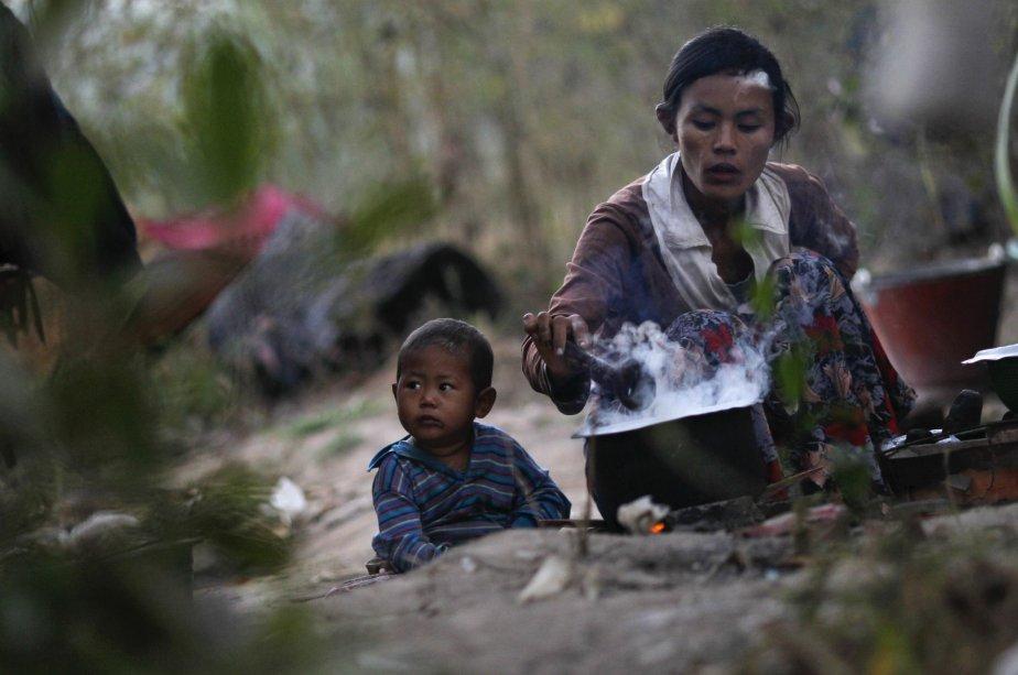 Un garçon assis près de sa mère pendant qu'elle cuit du riz dans un champ à l'extérieur de Rangoon, en Birmanie. | 18 janvier 2013