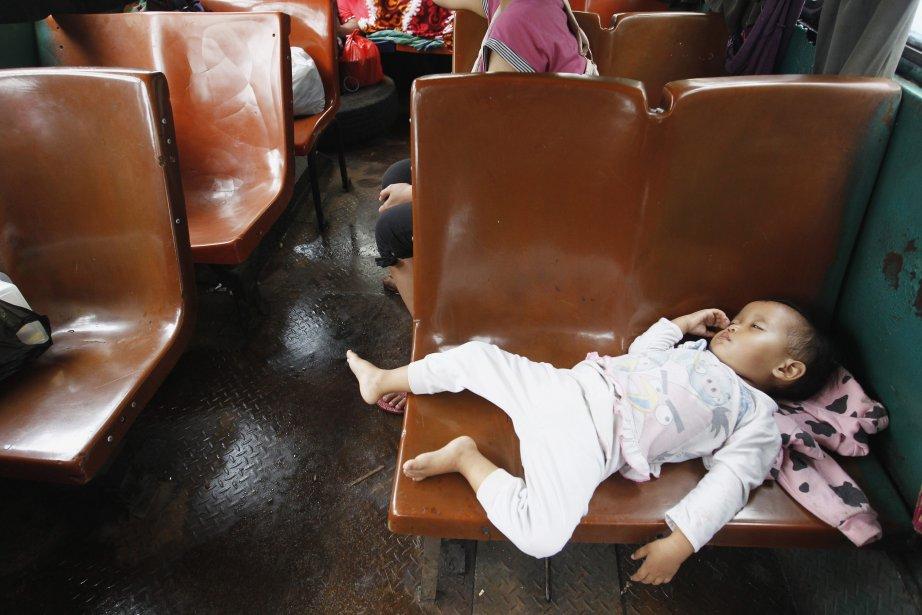 Un enfant dort dans un autobus public utilisé comme refuge  par les résidants qui ont fui leurs maisons inondées à Jakarta. | 18 janvier 2013