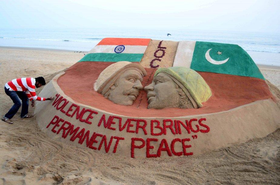 À Puri, à 65 km de la ville de Bhubaneswar, en Inde, un artiste indien met la touche finale à la sculpture de sable que lui ont inspirée les escarmouches le long de la frontière indo-pakistanaise. | 18 janvier 2013
