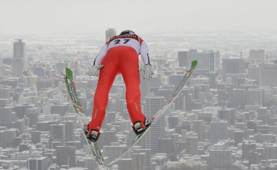 Le skieur russe Ilja Rosliakov s'élance au dessus de la ville de Sapporo, au Japon, lors de la Coupe du monde de saut à ski, dimanche. | 20 janvier 2013