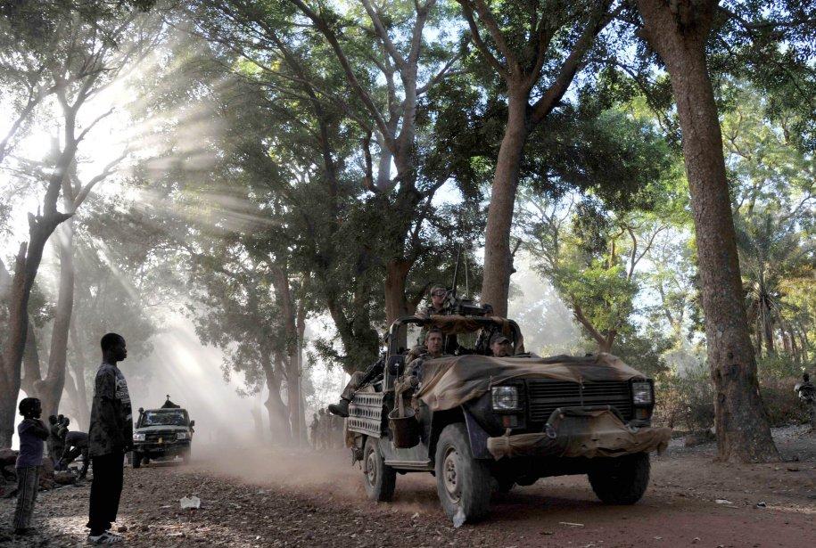 De jeunes Maliens observent le passage de soldats français dans une rue de Niono. Le ministre de la Défense de la France, Jean-Yves Le Drian, a déclaré que l'objectif de l'opération militaire française était de reconquérir l'entièreté du Mali, dont le Nord est sous la coupe de militants islamistes. «Nous ne laisserons aucune poche de résistance», a-t-il déclaré à la télévision. | 21 janvier 2013