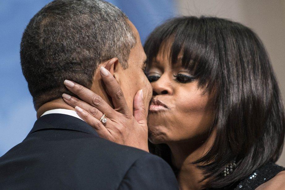 La première dame des États-Unis, Michelle Obama, embrasse son mari à une réception donnée pour l'investiture de ce dernier. Le 44e président des États-Unis et le vice-président Joseph R. Biden ont prêté serment dimanche, et la cérémonie d'investiture a lieu lundi. | 21 janvier 2013