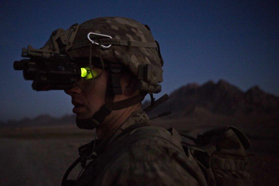 Un soldat américain utilise des jumelles de vision nocturne lors d'une rencontre avec la police afghane à un point de contrôle de l'avant-poste de Hutal, dans le district de Maywand (province de Kandahar), en Afghanistan. | 21 janvier 2013