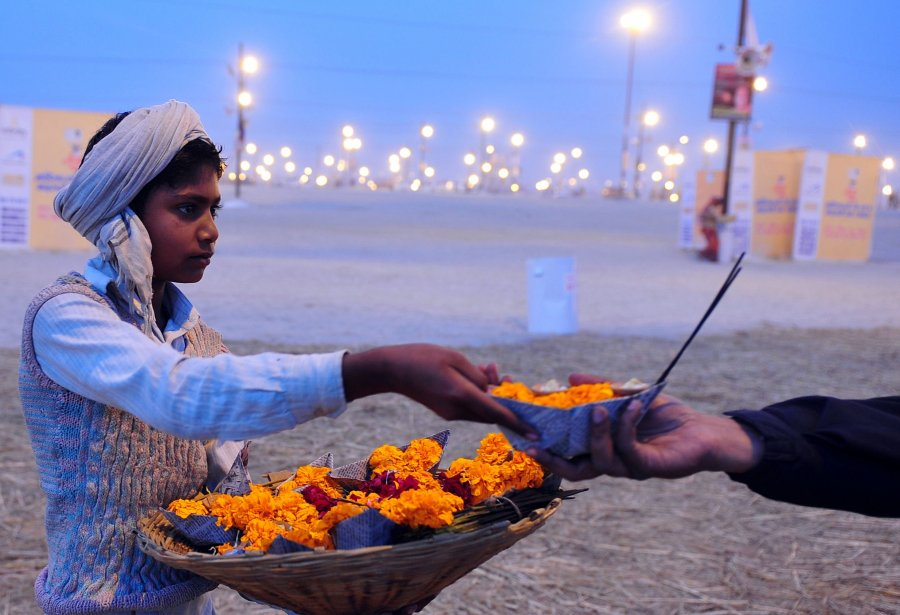 Un jeune Indien vend des fleurs au confluent du Gange... | 2013-01-22 00:00:00.000