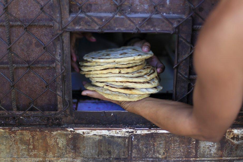 Un membre d'un puissant gang de rue reçoit une pile de tortillas dans une prison réservée aux détenus de 13 à 25 ans, à Tonacatepeque, au Mexique. Les chefs des gangs, détenus ailleurs, ont obtenu la permission de visiter cette prison pour parler de la trêve conclue en mars 2012 entre les deux gangs les plus puissants, la Mara Salvatrucha et le gang de la 18e Rue (Mara 18), selon les médias locaux. | 22 janvier 2013