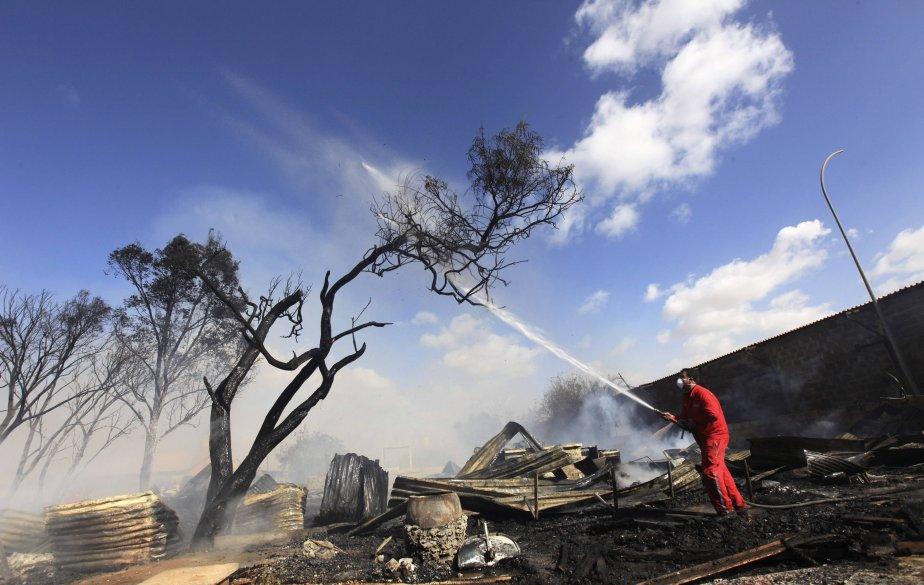 Un pompier combat un incendie qui s'est déclaré dans un camp pour familles sans abri à Benghazi, en Libye. | 23 janvier 2013