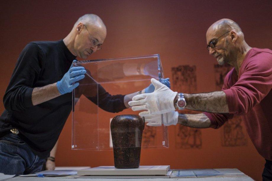 Marcel Marcotte (gauche), technicien aux installations et Richard Gagnier (droite), chef du services de la restauration, installent la protection sur un gobelet cérémoniel en bois peint, en forme de tête de félin de la civilisation inca datant du 18e siècle. | 24 janvier 2013