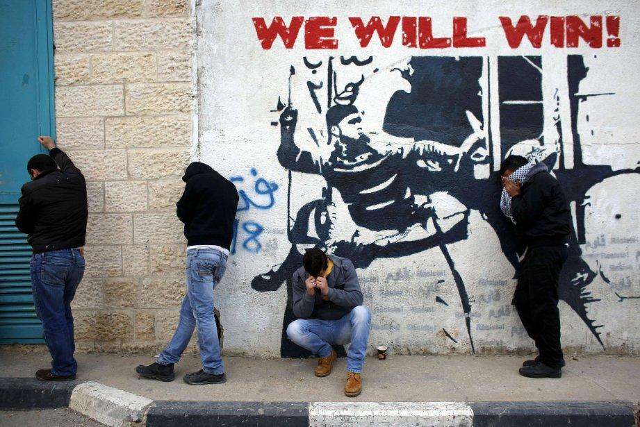 Des manifestants palestiniens se mettent à l'abri des gaz lacrymogènes à Bethléem, en Cisjordanie. | 25 janvier 2013