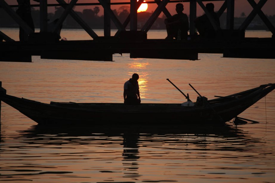 Un homme sur son embarcation sous un pont à Yangon | 28 janvier 2013