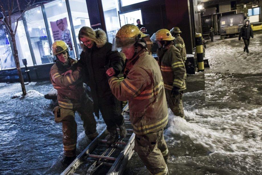 Des pompiers ont installé une échelle pour permettre l'évacuation sécuritaire d'un édifice. (Edouard Plante-Fréchette, La Presse)