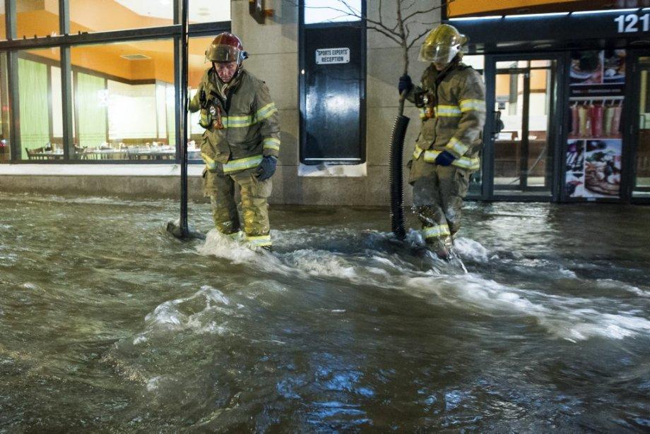 Deux pompiers traversent une importante coulée d'eau en se méfiant de la glace sous-jacente. (Edouard Plante-Fréchette, La Presse)