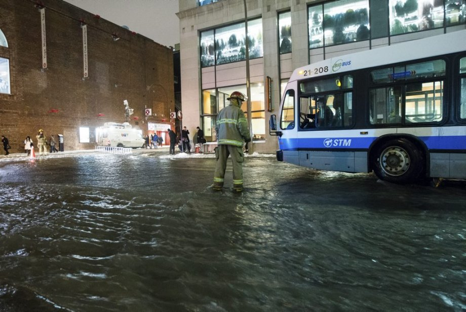Un pompier guide un autobus de la STM à travers une rue inondée. | 28 janvier 2013