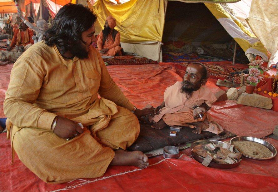 Mahadev Bharti 56 ans, un sadhu qui mesure 46 cm, en conversation avec un collègue dans une tente en bordure du Gange. | 29 janvier 2013