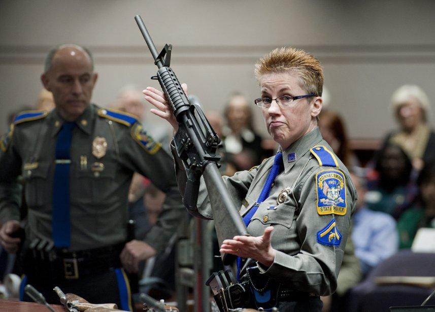 La détective Barbara J. Mattson, de la police du Connecticut, brandit une arme semblable à celle qu'a utilisée l'auteur de la  tuerie de Newtown, Adam Lanza, lors d'une audience publique à Hartford. | 29 janvier 2013