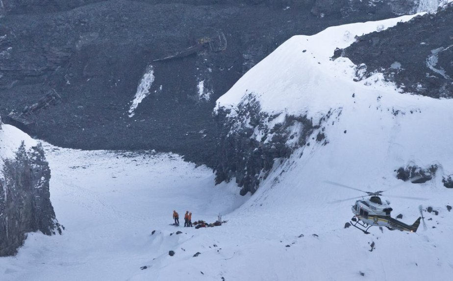 Les équipes de sauvetage s'affairaient en fin d'après-midi mardi dans le fond de la carrière de l'Épiphanie avec l'aide de l'hélicoptère de la Sûreté du Québec. On aperçoit les carcasses des deux véhicules ensevelis dans le coin supérieur gauche. Les recherches doivent se poursuivre en soirée jusqu'à la tombée de la pluie verglaçante. | 29 janvier 2013
