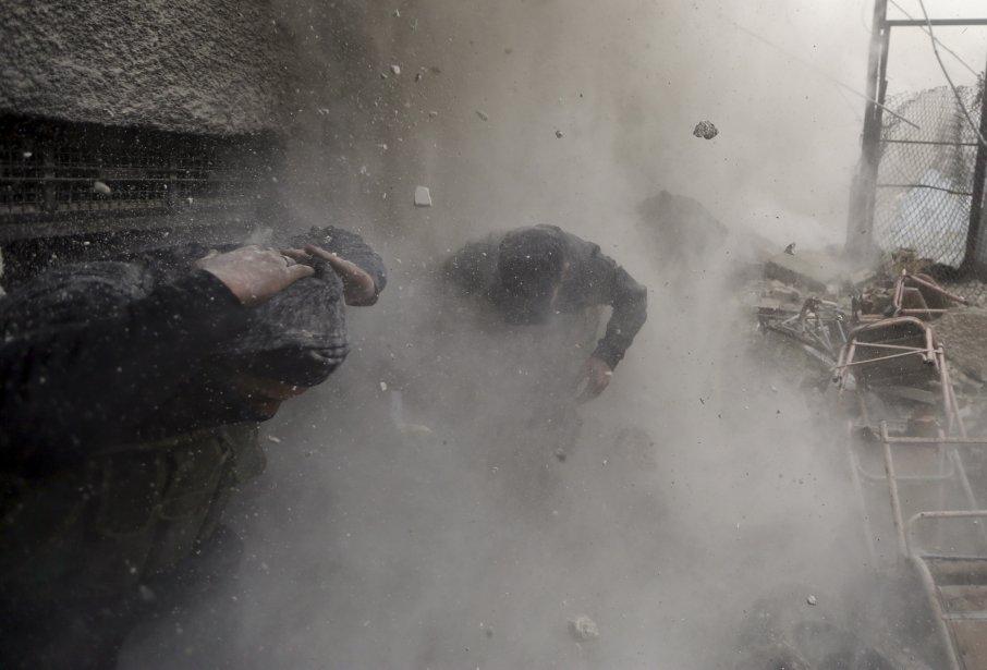 Les combattants de l'Armé syrienne libre courent se mettre à l'abri à Ain Tarma un quartier de Damas. | 30 janvier 2013