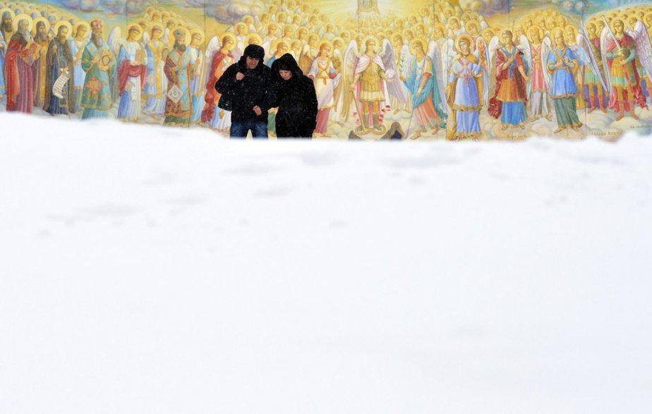 Un couple marche devant une fresque de la cathédrale Mykhaylo à Kiev, en Ukraine. | 31 janvier 2013