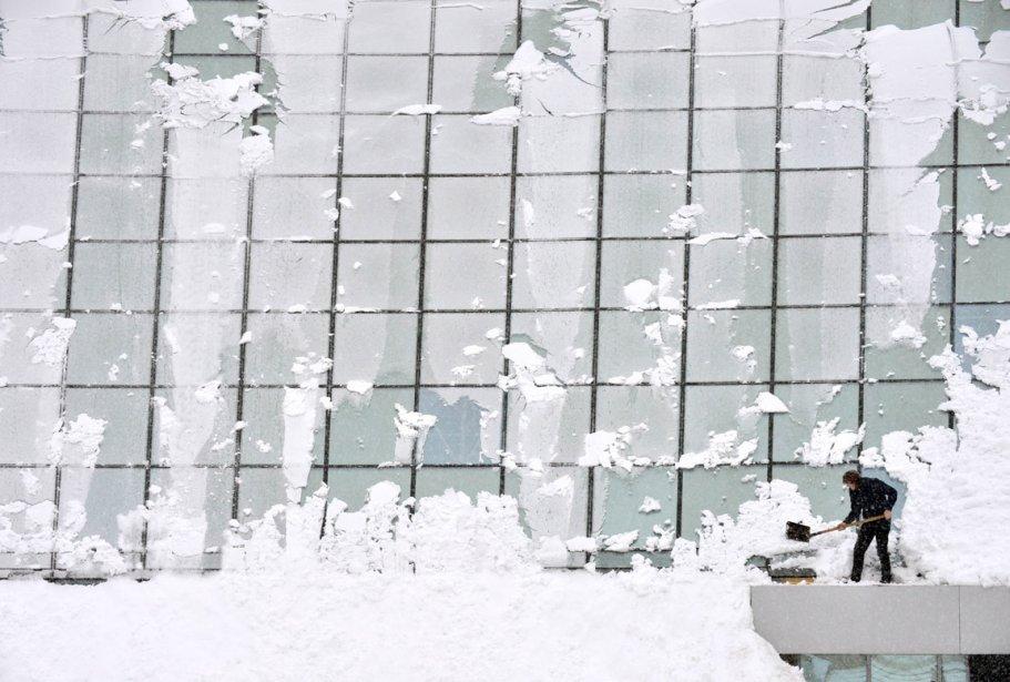 Un homme pellette de la neige depuis le toit d'un centre commercial de Kiev, en Ukraine. | 31 janvier 2013