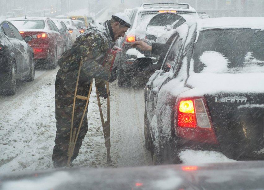 Un mendiant demande la charité aux automobilistes circulant dans cette rue de Kiev, lors d'une tempête de neige. | 31 janvier 2013