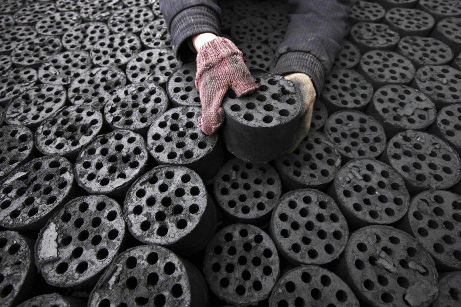 Un travailleur empile des briquettes de charbon sur un chariot à Hubei, en Chine. | 31 janvier 2013
