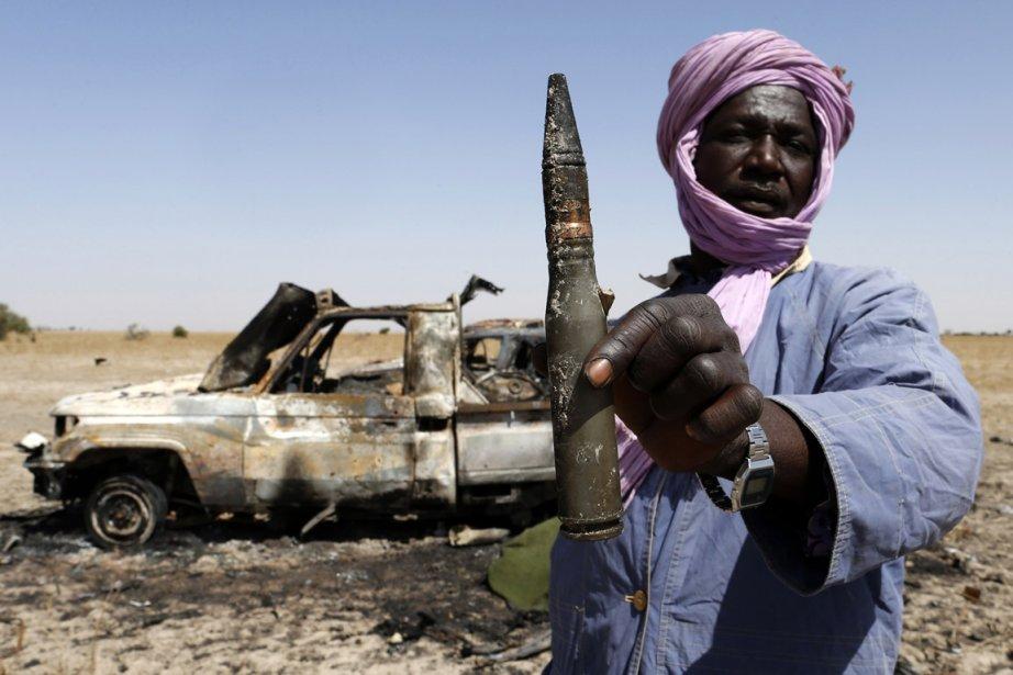 Un Touareg pose devant la carcasse d'une camionette appartenant aux rebelles islamistes sur la route entre Diabaly en Tombouctou, la roquette responsable de la destruction du véhicule à la main. | 31 janvier 2013