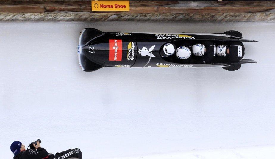 Un photographe s'installe pour prendre en photo l'équipe allemande de bobsleigh à quatre à St-Moritz en Suisse. | 31 janvier 2013