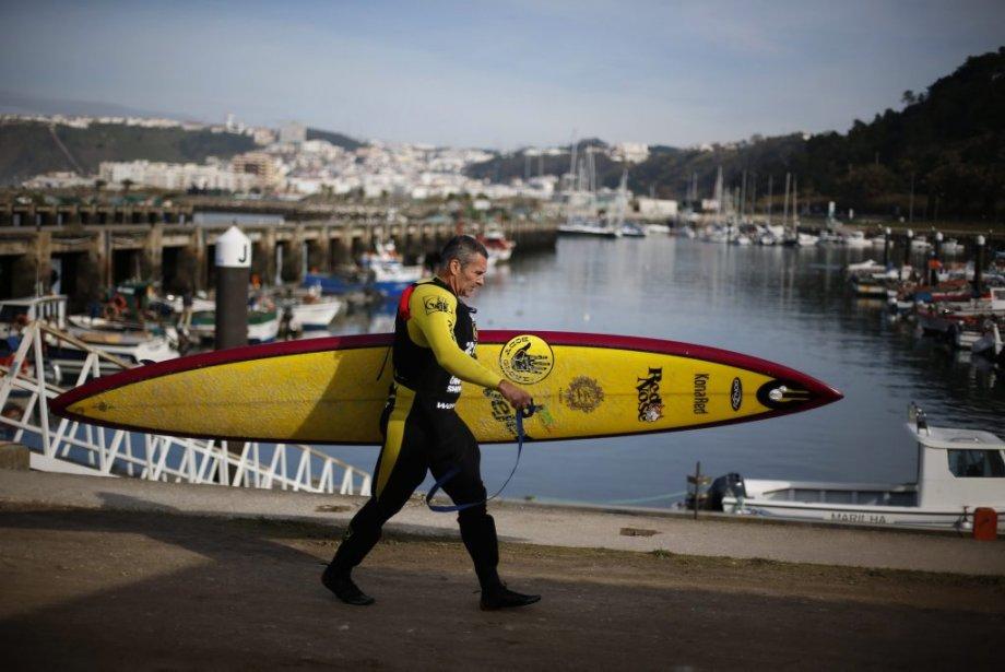 Garrett McNamara transporte sa planche de surf avant d'aller affronter... | 2013-01-31 00:00:00.000